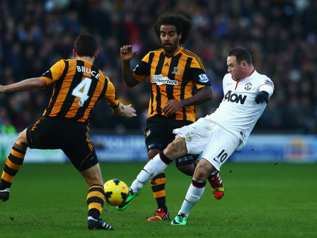 Wayne Rooney of Manchester United shoots and scores his sides second goal during the Barclays Premier League match between Hull City and Manchester United at KC Stadium on December 26, 2013