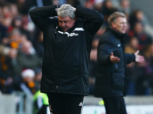 Hull City manager Steve Bruce and Manchester United manager David Moyes react on the touchline before the Barclays Premier League match between Hull City and Manchester United at KC Stadium on December 26, 2013