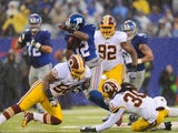 Wide receiver Jerrel Jernigan of the New York Giants avoids a tackle from inside linebacker Perry Riley and free safety E.J. Biggers of the Washington Redskins on December 29, 2013