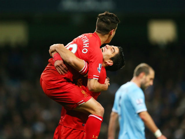 Luis Suarez of Liverpool congratulates goalscorer Philippe Coutinho during the Barclays Premier League match between Manchester City and Liverpool at Etihad Stadium on December 26, 2013