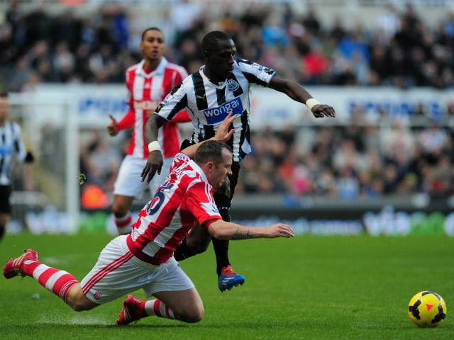 Newcastle player Moussa Sissoko tangles with Charlie Adam during the Barclays Premier League match between Newcastle United and Stoke City at St James' Park on December 26, 2013