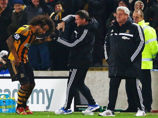 Tom Huddlestone of Hull City gets attention to his hair on the touchline after scoring during the Barclays Premier League match against Fulham on December 28, 2013