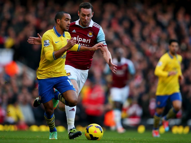 Theo Walcott of Arsenal is chased by Kevin Nolan of West Ham United during the Barclays Premier League match between West Ham United and Arsenal at Boleyn Ground on December 26, 2013