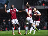 West Ham United's English striker Carlton Cole celebrates with teammates after scoring a goal during the English Premier League football match between West Ham United and Arsenal at the Boleyn Ground, Upton Park, in east London on December 26, 2013