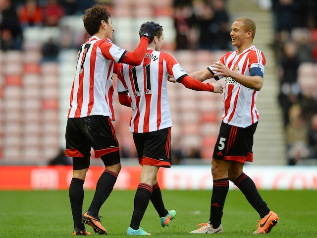 Adam Johnson of Sunderland celebrates with teammates Ji Dong-Won and Wes Brown after scoring the opening goal from a free kick during the game against Carlisle on January 5, 2014