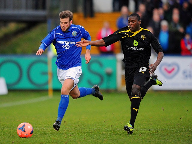 Macclesfield's Andy Halls and Sheffield Wednesday's Jeremy Helan in action during their FA Cup third round match on January 4, 2013