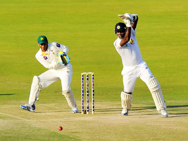 Sri Lankan batsman Angelo Mathews plays a shot as Pakistan wicketkeeper Younis Khan looks on during the fourth day of the first cricket Test match between Pakistan and Sri Lanka at the Sheikh Zayed Stadium in Abu Dhabi on January 3, 2014