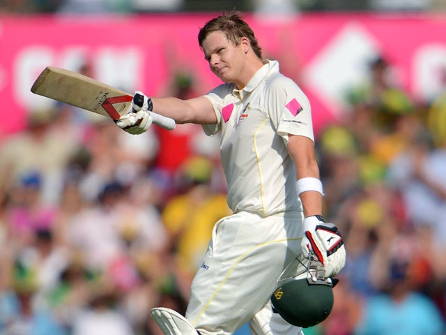 Australian batsman Steve Smith raises his bat after reaching his century on the first day of the fifth Ashes cricket Test against England at the Sydney Cricket Ground on January 3, 2014