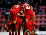 MK Dons' Ben Reeves is mobbed by teammates after scoring his team's second goal against Wigan during their FA Cup third round match on January 4, 2013