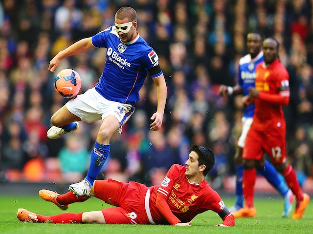 James Wesolowski of Oldham is tackled by Luis Alberto of Liverpool during the Budweiser FA Cup third round match on January 5, 2014