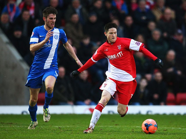 Kidderminster's Joe Lolley and Peterborough's Shaun Brisley in action during their FA Cup third round match on January 4, 2013