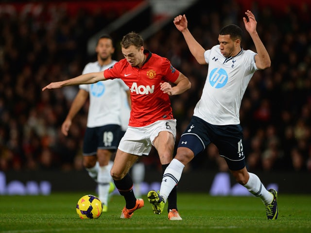 Jonny Evans of Manchester United competes with Etienne Capoue of Tottenham Hotspur during the Barclays Premier League match between Manchester United and Tottenham Hotspur at Old Trafford on January 1, 2014