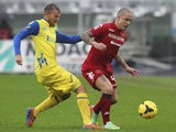 Radja Nainggolan (R) of Cagliari Calcio competes for the ball with Luca Rigoni (L) of AC Chievo Verona during the Serie A match on January 5, 2014