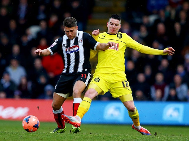 Grimsby's Scott Neilson and Huddersfield's Adam Hammill in action during their FA Cup third round match on January 4, 2013