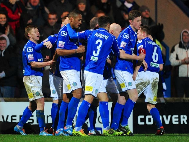 Macclesfield's Steve Williams is mobbed by teammates after scoring his team's opening goal against Sheffield Wednesday during their FA Cup third round match on January 4, 2013