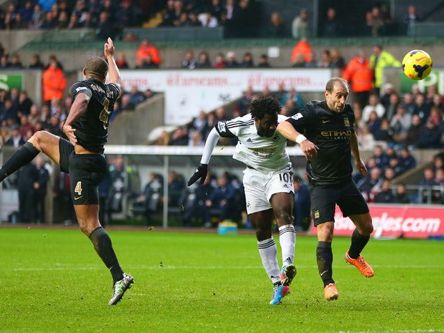 Wilfried Bony of Swansea City scores his sides opening goal as Pablo Zabaleta of Manchester City fails to challenge during the Barclays Premier League match between Swansea City and Manchester City at the Liberty Stadium on January 1, 2014
