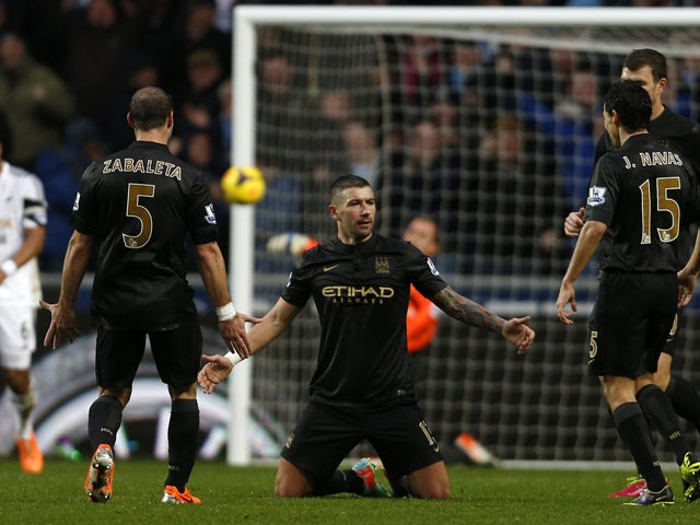 Manchester City's Serbian defender Aleksandar Kolarov celebrates with teammates after scoring their third goal during the English Premier League football match between Swansea City and Manchester City at The Liberty Stadium in Swansea, south Wales on Janu