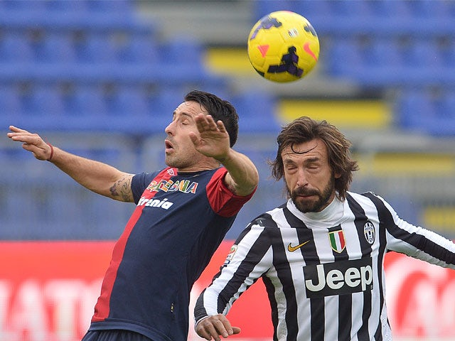 Cagliari's Andrea Cossu and Juventus' midfielder Andrea Pirlo battle for the ball during their Serie A match on January 12, 2014