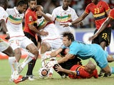Angolan goalkeeper Carlos and his teammate Kali try to make save from Mali strikers Seydou Keita and Mamadou Bagayoko at the opening match of African Cup of Nations football championships CAN2010 between Angola and Mali at the November 11 stadium in Angol