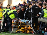 West Ham manager Sam Allardyce checks on the wellbeing of player Guy Demel who is stretchered off during the Barclays Premier League match between Cardiff City and West Ham United at Cardiff City Stadium on January 11, 2014