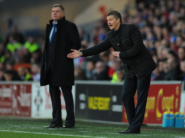 New Cardiff manager Ole Gunnar Solskjaer reacts as Sam Allardyce looks on during the Barclays Premier League match between Cardiff City and West Ham United at Cardiff City Stadium on January 11, 2014