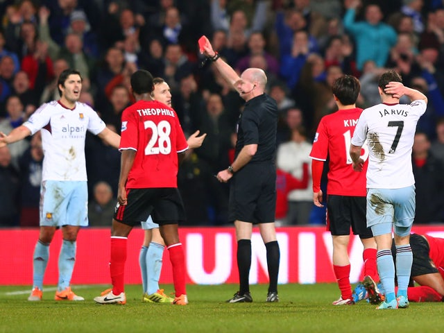 James Tomkins of West Ham United is shown a red card by referee Lee Mason duering the Barclays Premier League match between Cardiff City and West Ham United at the Cardiff City Stadium on January 11, 2014