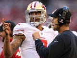 Colin Kaepernick of the San Francisco 49ers talks with head coach Jim Harbaugh on the sidelines against the Arizona Cardinals on January 5, 2014