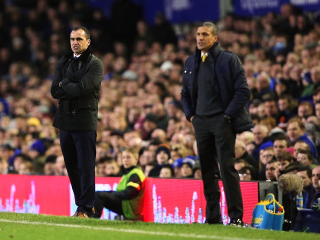 Roberto Martinez, manager of Everton looks on with Chris Hughton, manager of Norwich City during the Barclays Premier League match between Everton and Norwich City at Goodison Park on January 11, 2014