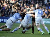 Toulouse's Jean-Marc Doussain is tackled by Saracens players during their Heineken Cup match on January 12, 2014