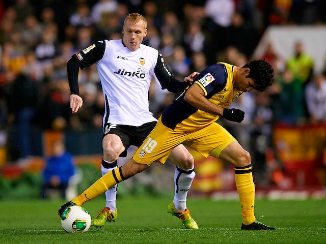 Jeremy Mathieu (L) of Valencia competes for the ball with Diego Costa of Atletico de Madrid during the Copa del Rey round of 16 first leg match on January 7, 2014