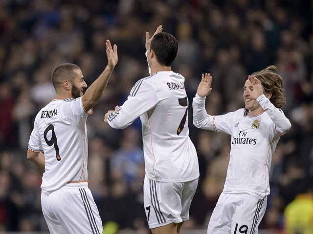 Real's Karim Benzema celebrates with teammates Cristiano Ronaldo and Luka Modric after scoring the opening goal against Osasuna during their Copa del Rey match on January 9, 2014