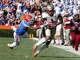 Kelvin Benjamin #1 of the Florida State Seminoles runs past Vernon Hargreaves III #1 of the Florida Gators during the game on November 30, 2013