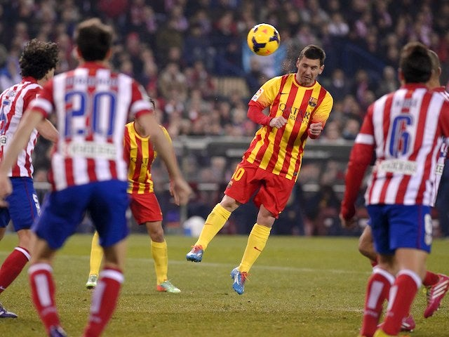 Barcelona's Argentinian forward Lionel Messi heads the ball during the Spanish league football match Club Atletico de Madrid vs FC Barcelona at the Vicente Calderon stadium in Madrid on January 11, 2014