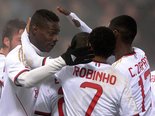 Mario Balotelli of AC Milan celebrates with team-mates after scoring their first goal during the Serie A match between US Sassuolo Calcio and AC Milan on January 12, 2014