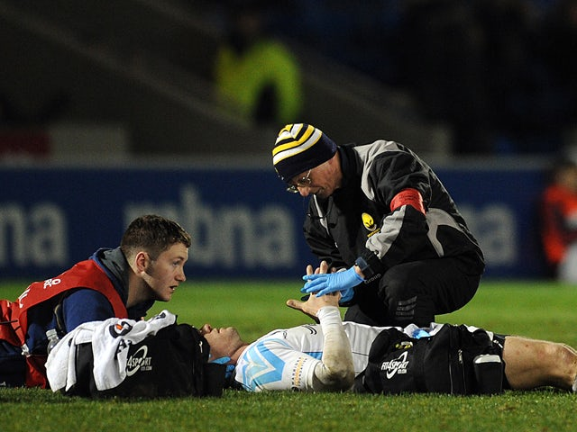 Paul Warwick of Worcester Warriors receives treatment on the field during the Amlin Challenge Cup match between Sale Sharks and Worcester Warriors at the AJ Bell Stadium on January 10, 2014