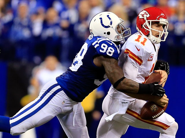 Outside linebacker Robert Mathis #98 of the Indianapolis Colts forces a fumble by quarterback Alex Smith #11 of the Kansas City Chiefs during a Wild Card Playoff game at Lucas Oil Stadium on January 4, 2014