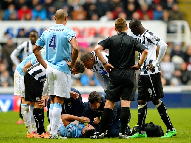 Samir Nasri of Manchester City receives medical attention after the tackle from Mapou Yanga-Mbiwa of Newcastle during the Barclays Premier League match on January 12, 2014