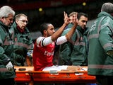 Theo Walcott of Arsenal makes a 2-0 gesture to the Tottenham fans as he is stretchered off the pitch during the Budweiser FA Cup third round match between Arsenal and Tottenham Hotspur at Emirates Stadium on January 4, 2014