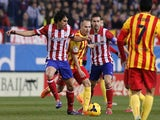 Atletico Madrid's Portuguese midfielder Tiago Mendes (L) vies with Barcelona's midfielder Andres Iniesta (C) during the Spanish league football match on January 11, 2014