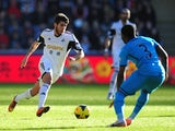 Swansea's Alejandro Pozuelo runs at Tottenham's Danny Rose during their Premier League match on January 19, 2014