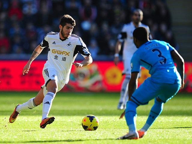 Swansea's Alejandro Pozuelo runs at Tottenham's Danny Rose during their Premier League match on January 19, 2014