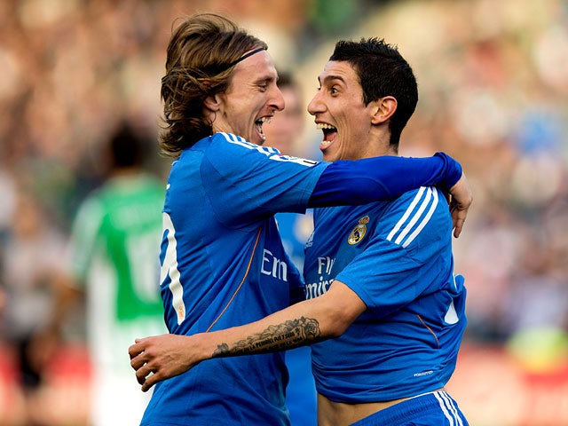 Real's Angel Di Maria celebrates with teammate Luka Modric after scoring his team's fourth goal against Real Betis during their La Liga match on January 18, 2014
