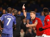 Referee Phil Dowdpoints off-field as Manchester United's Serbian defender Nemanja Vidic pleads after being shown a straight red card for a challenge on Chelsea's Belgian midfielder Eden Hazard during the English Premier League football match between Chels