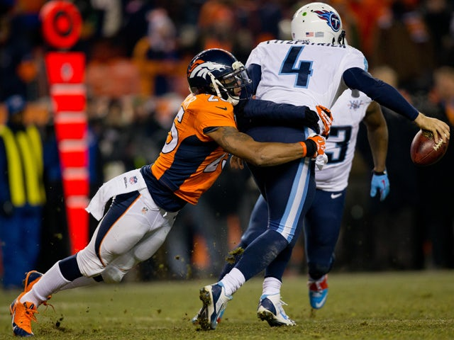 Cornerback Chris Harris #25 of the Denver Broncos tries to tackle quarterback Ryan Fitzpatrick #4 of the Tennessee Titans late in the fourth quarter at Sports Authority Field Field at Mile High on December 8, 2013