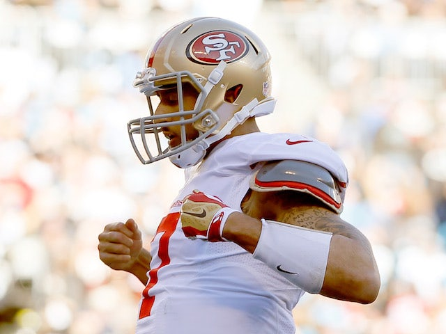 Colin Kaepernick of the San Francisco 49ers celebrates after a touchdown in the third quarter against the Carolina Panthers during the NFC Divisional Playoff Game on January 12, 2014