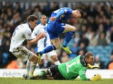 Leicester's David Nugent jumps over Leeds goalkeeper Paddy Kenny as he scores the opening goal during their Championship match on January 18, 2014