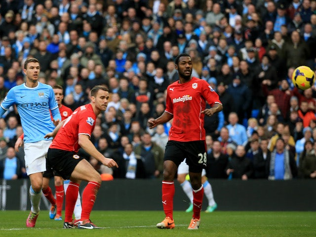 Edin Dzeko of Manchester City scores the opening goal with a header during the Barclays Premier League game against Cardiff City on January 18, 2014