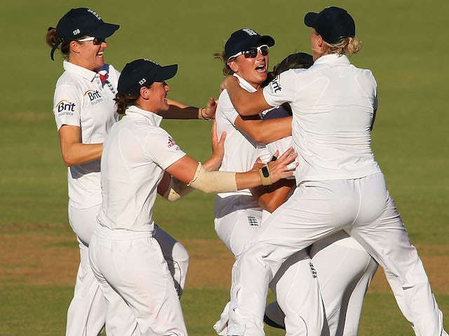 Sarah Taylor and Jennifer Gunn of England celebrate with team mates after the stumping of Jodie Fields of Australia during day three of the Women's Ashes Test on January 12, 2014