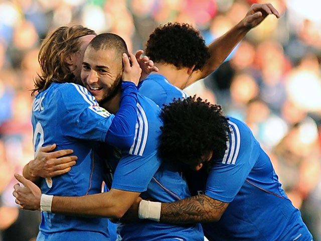 Real's Karim Benzema is congratulated by teammates after scoring his team's third goal against Real Betis during their La Liga match on January 18, 2014