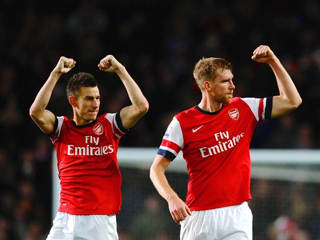 Laurent Koscielny of Arsenal and Per Mertesacker of Arsenal celebrate victory at the final whistle during the Barclays Premier League match between Arsenal and Liverpool at Emirates Stadium on November 2, 2013